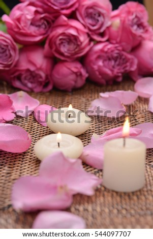 pink rose and petals with candle on mat