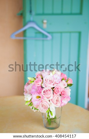 Pink roses flowers in vase on turquoise background against wall.
