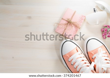 Pink sport shoes on a white background with a pink bouquet, perfume bottle and pink notebook. View from above