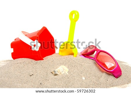 pink sunglasses and beach toys over white background