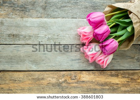 Pink tulips in bouquet on wooden background.  Beautiful green tulips petals, tulips on wood.