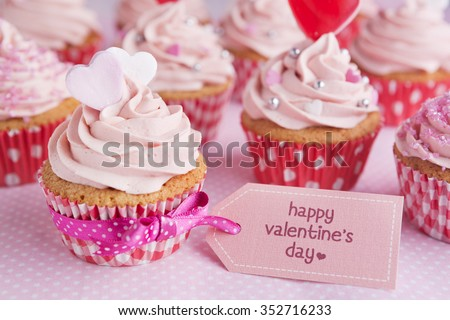 Pink Valentine cupcakes with the words 'Happy Valentine's day' on a tag.