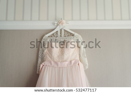 Pink wedding dress hanging on a hanger. Close-up.