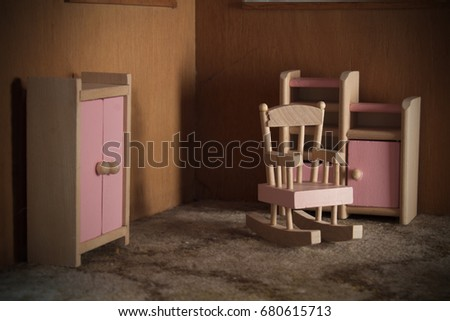 Pink Wooden Rocking Chair Next To A Wardrobe And Cabinet. Light From The  Right Side