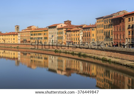 PISA, ITALY - SEPTEMBER 21, 2015 : View of historical buildings along the river in Pisa, Italy on bright blue sky background.