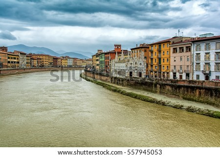 Pisa (Tuscany, Italy) - Church of Santa Maria della Spina and colorful houses along the Arno river, with dramatic sky.