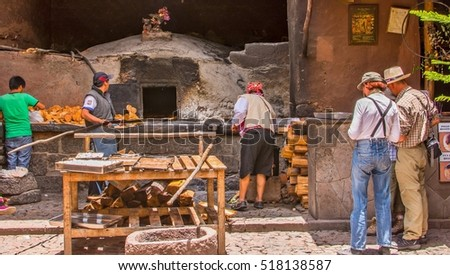 PISAC, PERU - OCTOBER 30, 201:  Tourists wait for empanadas to bake in an ancient oven in Pisac, Peru.
