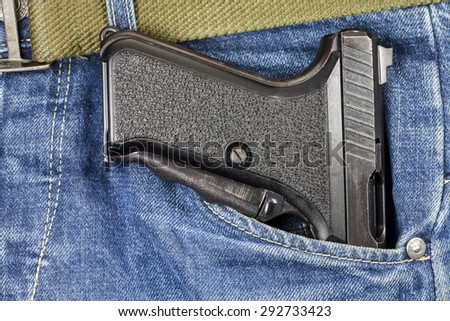 Pistol in the pocket of jeans.