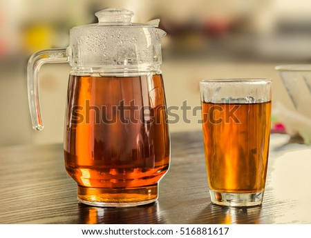Pitcher and glass of hot black tea on kitchen background.