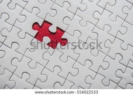 Placing missing a piece of puzzle. Plain white jigsaw puzzle on Red background. Puzzle game. exception to the rule.