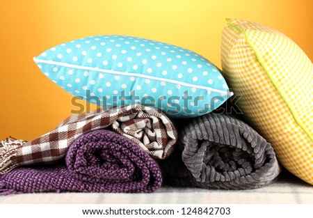 Plaids and color pillows on yellow background