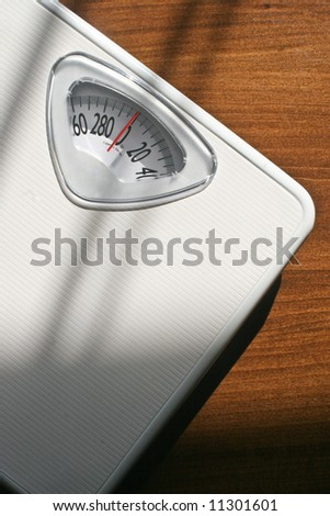 Plain white bathroom scale on a wood floor. Vertically framed shot