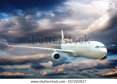 Plane is flying in the sky among light and dark clouds.