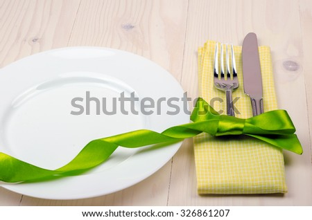plate, fork and knife decorated with green ribbon