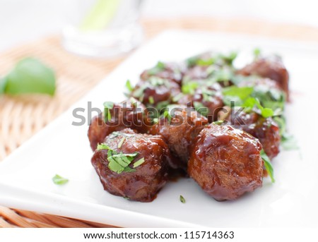 Plate of meatballs in gravy with herbs horizontal