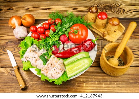 Plate with sliced fresh pork lard, fresh produce, vegetables on the wooden table