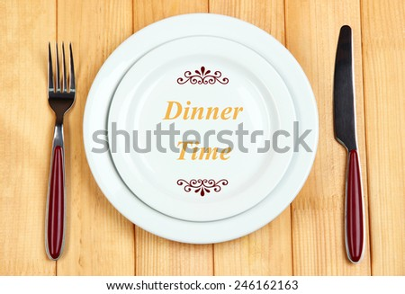 "Plate with text ""Dinner Time"", fork and knife on wooden background"