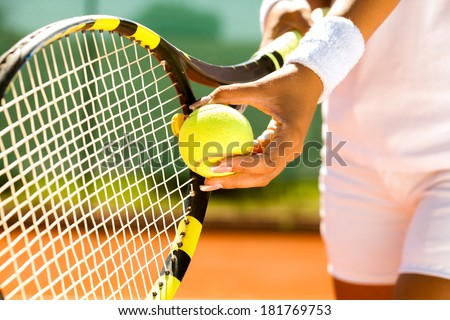 Player's hand with tennis ball preparing to serve