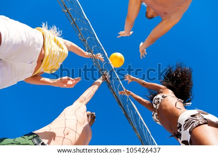 Players doing summer sports trying to block a dangerous attack in a beach volleyball game