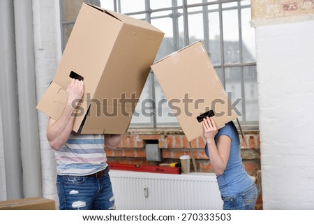Playful couple wearing brown cardboard boxes over their head squaring off in their new home during the process of renovating and moving house