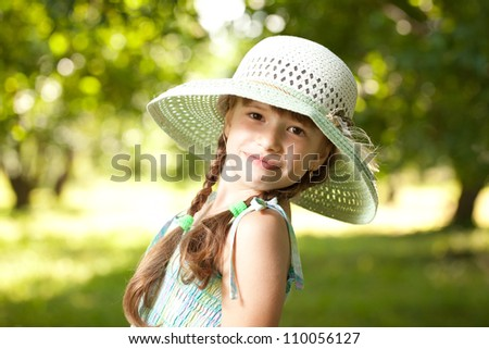 Playful girl in a hat and light clothes