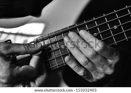 Playing a guitar with emphasis on hands and strings