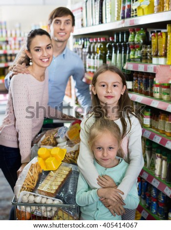 Pleasant happy charming customers with children buying food in hypermarket and smiling