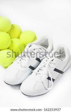 Plenty of Tennis Balls Along with Sneakers Isolated Over White Background