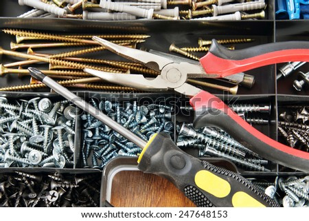 Pliers and screwdriver lie on a plastic box with many various screws