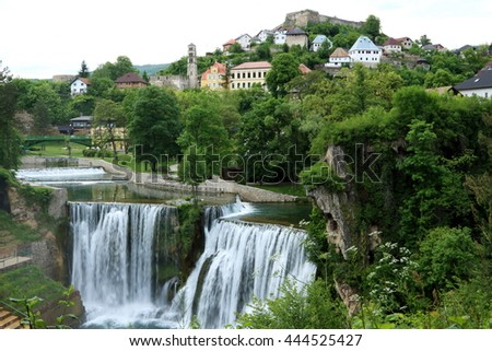 Pliva Waterfall in Jajce in Bosnia and Herzegovina, with water rushing down the 20m height cliff, with the old town in the background