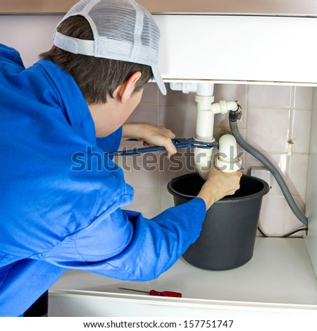 plumber in working clothes fixing a drain
