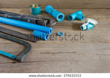 Plumbing tool pipes and equipment on wood background