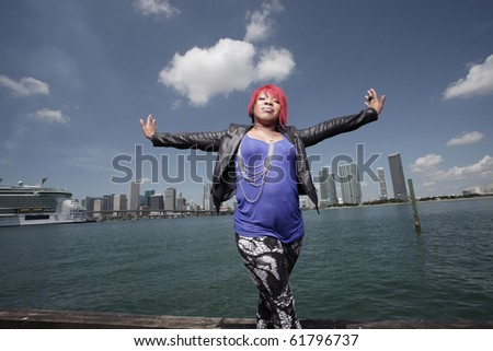 Plus size woman posing by the bay with arms outstretched