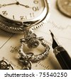 Pocket watch and fountain pen on financial report - stock photo