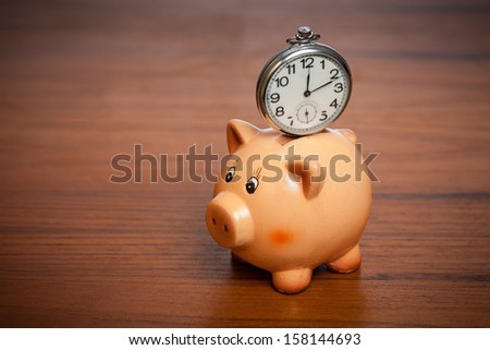 Pocket watch on a piggy bank on a brown table