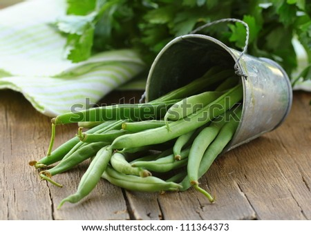 pods of green peas on a wooden table, rustic style