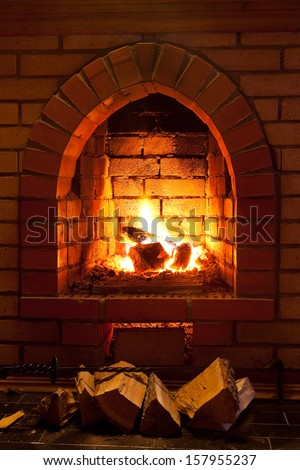 poker, firewood and flames of fire in fireplace in evening time