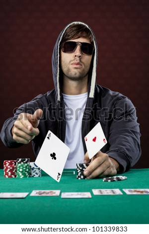 Poker player, on a red background, throwing two ace cards.