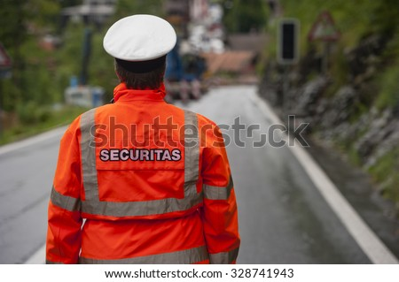 Police in hi-visibility jackets, securitas traffic control on the road.