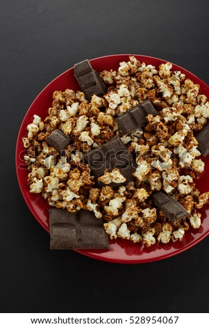popcorn chocolate in a red plate top view on black backgrounds with bars of chocolate