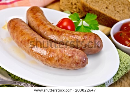 Pork sausages fried in a dish, bread, sauce, tomato, parsley, fork, knife, napkin on the background of wooden boards