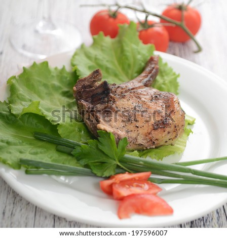 pork steak on lettuce with tomatoes