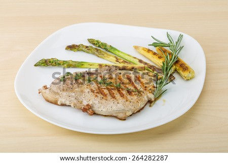 Pork steak with grilled asparagus and baby corn