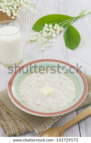Porridge with butter in a bowl on a wooden table