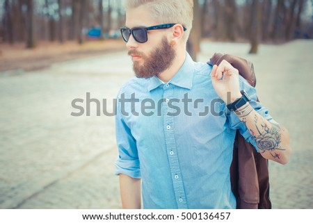Portait of a stylish blond hipster man in shirt and fashionable glasses.