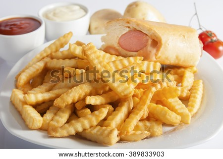 Portion of French fries (Crinkle-cut) deep fried, served on a white plate with hot dog next to white bowl with mayonnaise and ketchup.