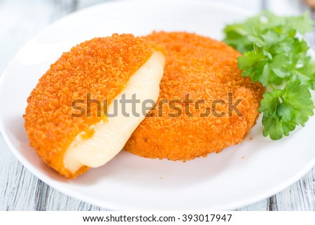 Portion of fried Camembert (selective focus) on a wooden table
