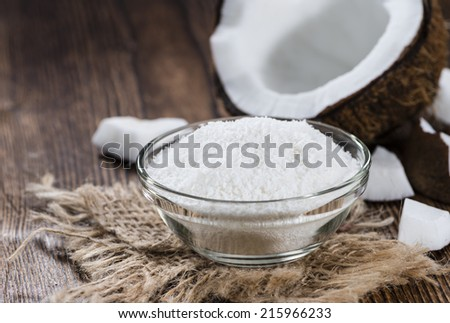 Portion of Grated Coconut on wooden background (close-up shot)