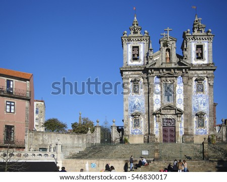Porto, Portugal - December 30, 2016: Saint Ildenfonso church in Porto. The church is adorned by white tiles painted in azure. Some people are visible on the stairs in front of the church.