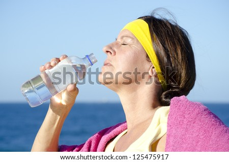 Portrait attractive fit and healthy, sporty and exercising, active retired mature woman drinking water out of bottle outdoor, isolated with ocean and blue sky as blurred background.